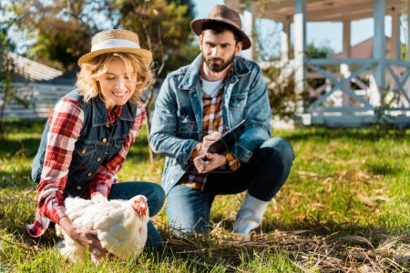 selective focus of woman holding chicken while her boyfriend writing in clipboard at farm