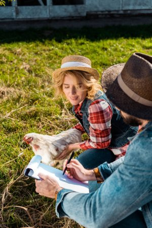 high angle view of woman holding chicken while her boyfriend making notes in clipboard at farm