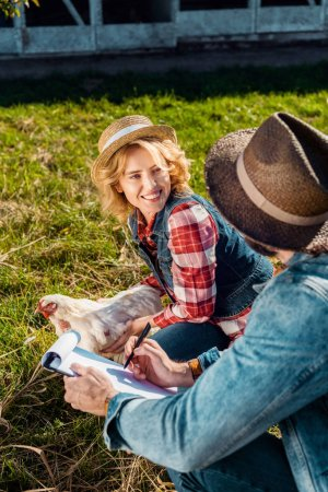 cheerful woman holding chicken while her boyfriend making notes in clipboard at farm