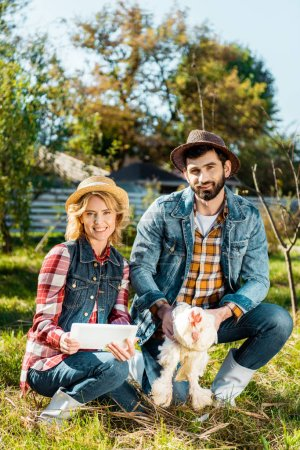 farmer holding chicken while his girlfriend using digital tablet near at ranch