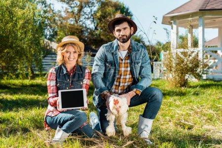 Photo pour Femme montrant tablette numérique avec écran blanc tandis que son petit ami tenant le poulet à la ferme - image libre de droit