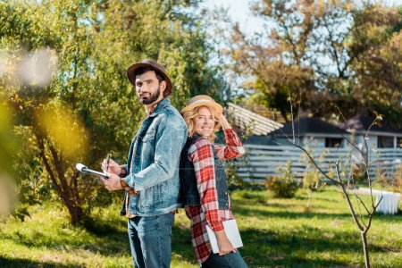 adult couple of farmers standing back to back with digital tablet and clipboard at ranch