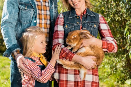 partial view of farmer family with little daughter and brown rabbit outdoors