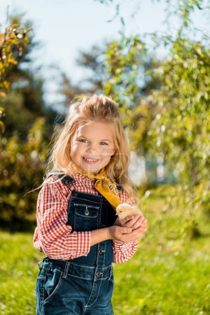 cheerful little kid holding adorable yellow baby chick outdoors