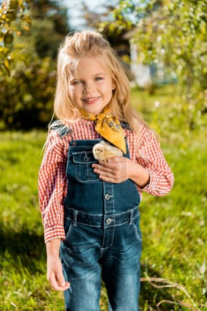 selective focus of child holding adorable yellow baby chick outdoors