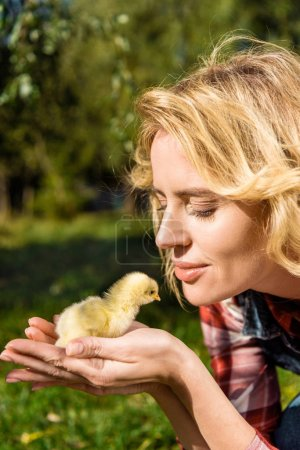 smiling woman holding adorable yellow baby chick outdoors