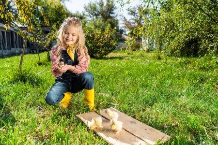 happy child sitting on grass near yellow baby chicks at farm