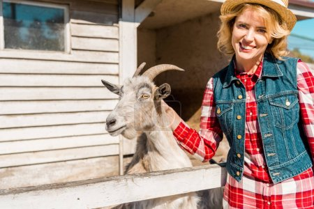 cheerful attractive woman touching goat near wooden fence at farm