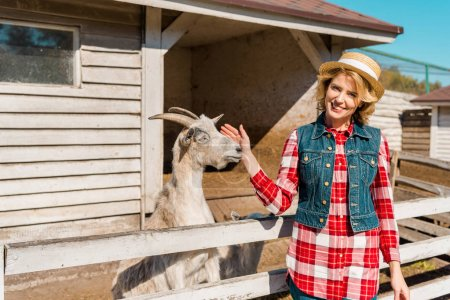 adult female farmer touching goat near wooden fence at ranch