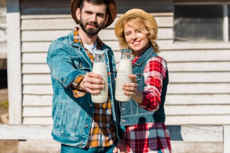 selective focus of couple of farmers in straw hats showing bottles of milk at ranch