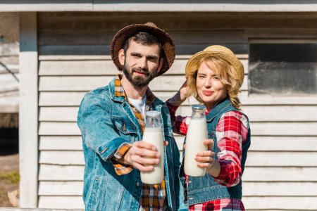 adult couple of farmers in straw hats showing bottles of milk at ranch
