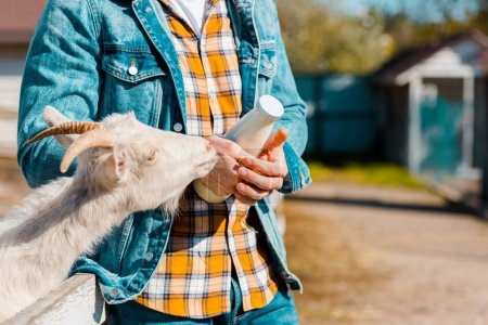 cropped image of male farmer with bottle of milk and goat standing near wooden fence at farm