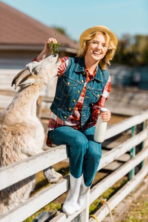 cheerful female farmer with milk bottle sitting on wooden fence and feeding goat at ranch