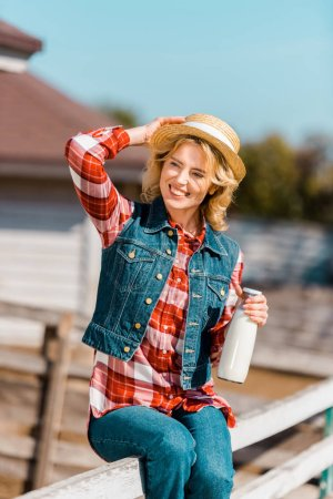 Photo for Selective focus of smiling female farmer holding bottle of milk and sitting on wooden fence at ranch - Royalty Free Image