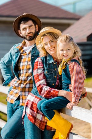 selective focus of happy farmer family with little daughter sitting on wooden fence at ranch