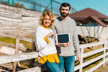 adult couple of farmers showing digital tablet with blank screen near wooden fence at farm