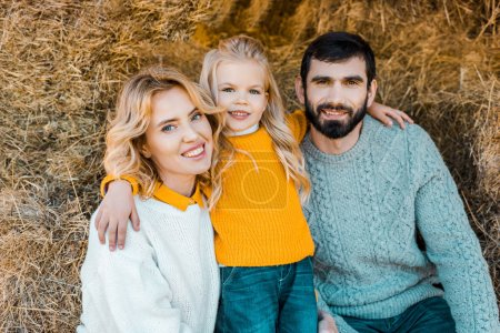 portrait of happy farmer family sitting on hay stacks at ranch