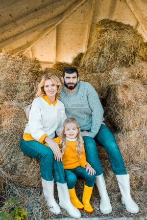 Photo for Cheerful farmer family with daughter sitting on hay stacks at ranch - Royalty Free Image