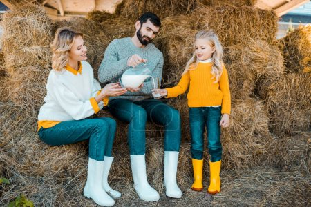 adult male farmer pouring milk to little daughter while his wife sitting near at ranch