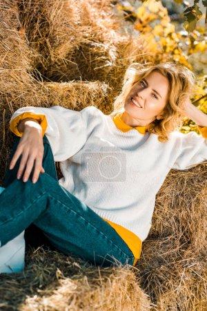 Photo for Smiling woman looking at camera and laying on hay stacks at ranch - Royalty Free Image