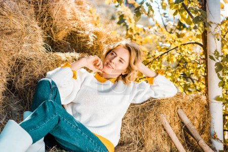dreamy female farmer looking away and laying on hay stacks at ranch