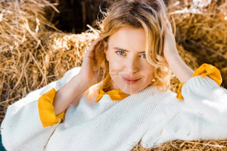 Photo for Close up portrait of beautiful woman looking at camera and laying on hay stacks at farm - Royalty Free Image