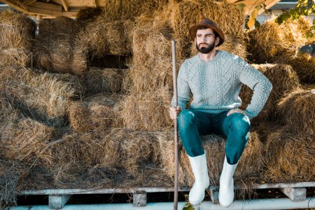 thoughtful male farmer in sweater and straw hat sitting on hay stacks at ranch