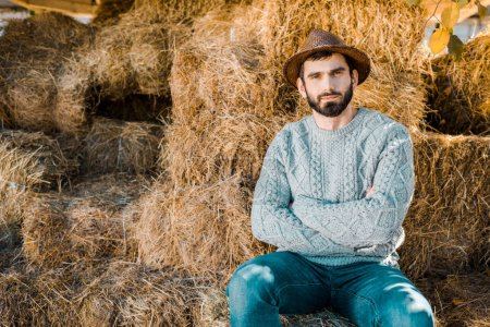 confident male farmer in sweater and straw hat sitting with crossed arms on hay stacks at ranch