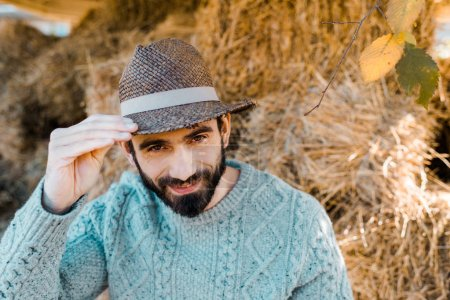 portrait of male farmer in sweater and straw hat looking at camera near hay stacks at farm