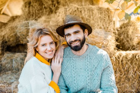 portrait of happy couple of farmers looking at camera while sitting on stacks of hay at farm