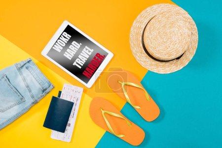"""Foto de Vista superior de naranja ojotas, pasaportes, billetes, tableta digital y ropa de colores de fondo. Elementos esenciales de vacaciones. Letras - """"trabajo duro. Viaje más difícil - Imagen libre de derechos"""