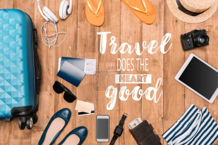 "Photo for Planning for trip set of travel accessories on wooden floor. Travel background with luggage, shoes, passports, flip flops, hat, camera. ""Travel does the heart good"" - lettering - Royalty Free Image"