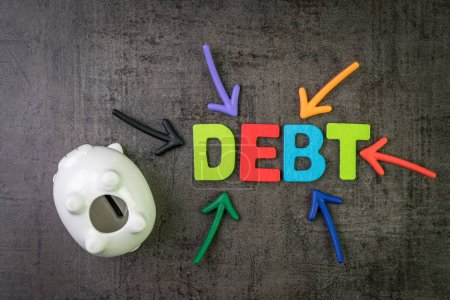 Photo for Debt, financial obligation that you borrow money and have to pay back concept, piggy bank with multi color arrows pointing to the word Debt at the center of black cement chalkboard wall. - Royalty Free Image
