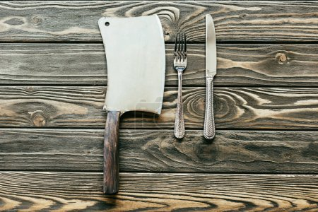 Photo for Silverware set and cleaver on wooden table - Royalty Free Image