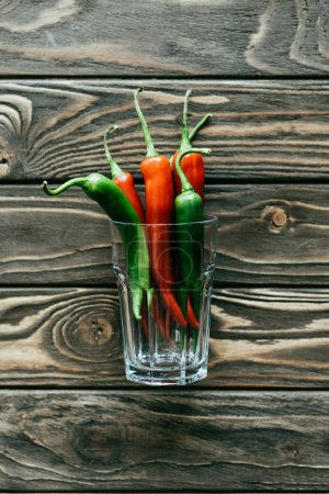 Green and red chili peppers in glass on wooden table