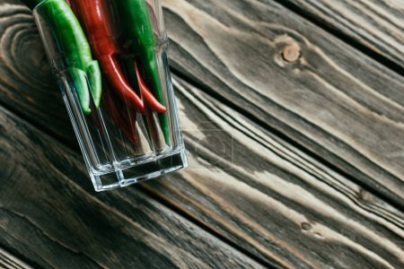 Close-up of glass with hot peppers on wooden table
