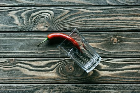 Red chili pepper in glass on wooden table