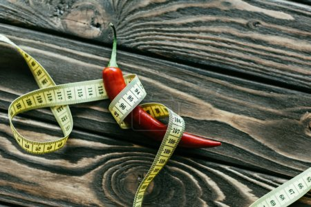 Red chili pepper with measuring tape on wooden table
