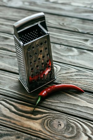 Red chili pepper with metal grater on wooden table