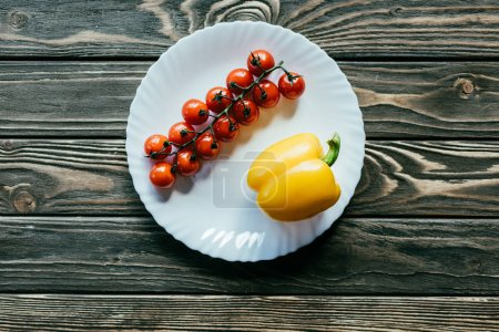 Cherry tomatoes and bell pepper on white plate on wooden table