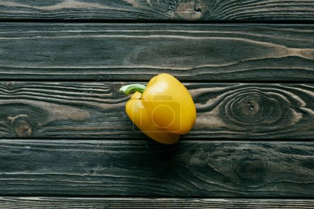 Yellow bell pepper on wooden table