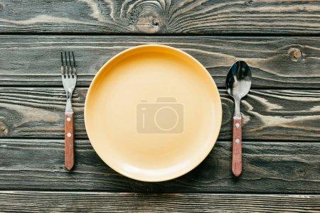 Teller mit Besteck auf Holztisch