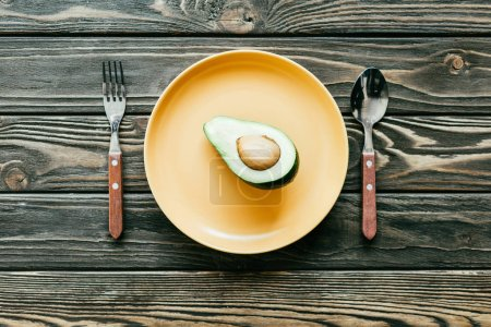 Photo for Avocado served on plate with spoon and fork on wooden table - Royalty Free Image