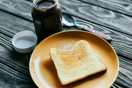 Toasted bread and chocolate spread on wooden table