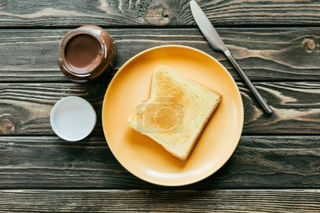 Slice of toast and chocolate spread on wooden table