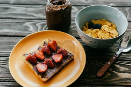 Corn flakes and toast with strawberries and chocolate butter on wooden table