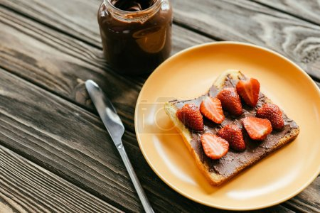 Toast with strawberries and chocolate spread on wooden table
