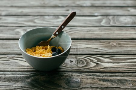Breakfast with corn flakes and blueberries in bowl on wooden table