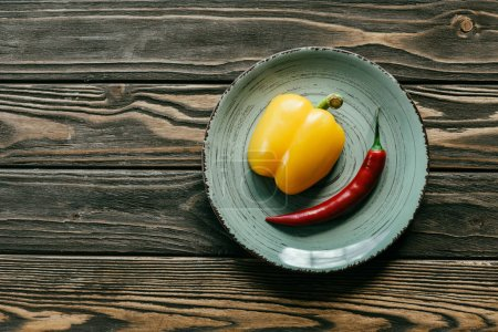 Yellow bell and red chili pepper in plate on wooden table