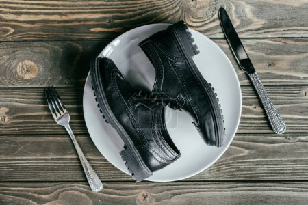 Shoes lying on plate with cutlery on wooden table